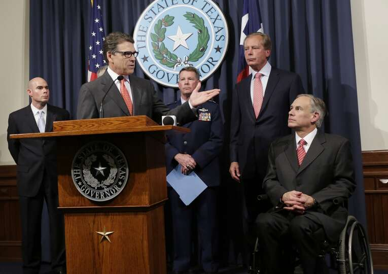 Attorney General Greg Abbott, right, listens as Gov. Rick Perry, at podium, speaks during a news con