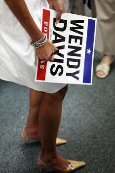 Sen. Wendy Davis signs a yard sign for a supporter Thursday, July 24, 2014 as she stops by the Nueces County Democratic Party headquarters to greet campaign phone bank volunteers in Corpus Christi, Texas. The gubernatorial candidate was in town to attend the Minority Advancement Project's annual shrimp boil fundraiser. (AP Photo/Corpus Christi Caller-Times, Michael Zamora) Photo: Michael Zamora, Associated Press