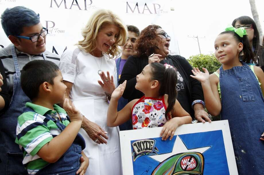 Sen. Wendy Davis greets a group of young artists Thursday, July 24, 2014 who created Loteria paintings to sell as a fundraiser during the Minority Advancement Project's annual shrimp boil at Heritage Park in Corpus Christi, Texas. The gubernatorial candidate also stopped by the Nueces County Democratic Party headquarters to greet phone bank volunteers. (AP Photo/Corpus Christi Caller-Times, Michael Zamora) Photo: Michael Zamora, Associated Press