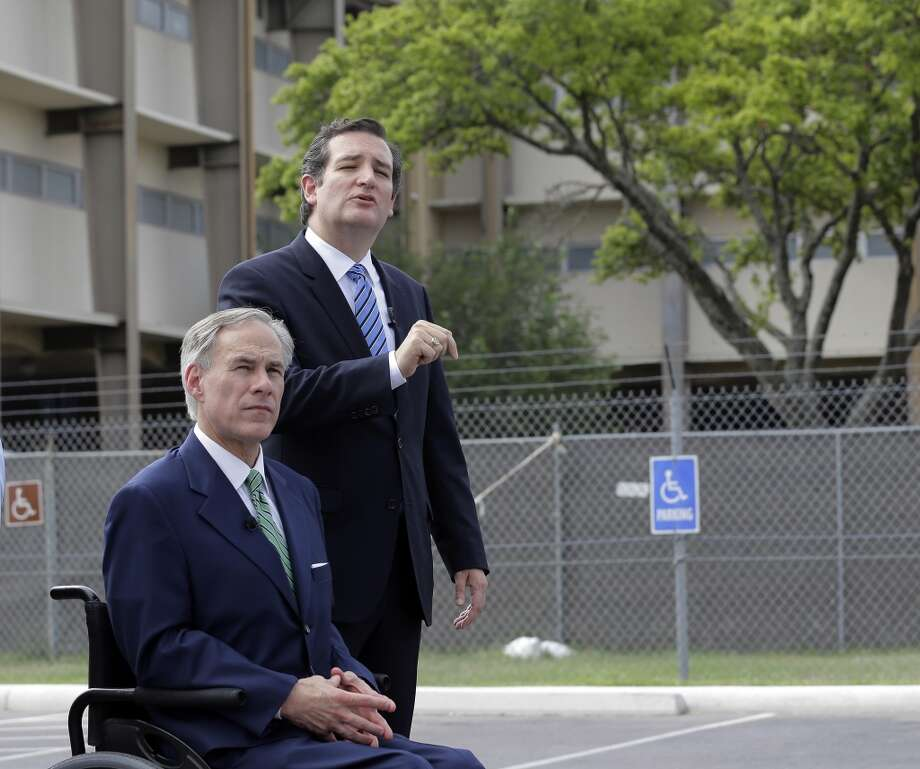 U.S. Sen. Ted Cruz, right, with Attorney General and Republican gubernatorial candidate Greg Abbott, talks to the media outside a temporary shelter for unaccompanied minors who have entered the country illegally at Lackland Air Force Base, Monday, June 23, 2014, in San Antonio. (AP Photo/Eric Gay) Photo: Eric Gay, Associated Press