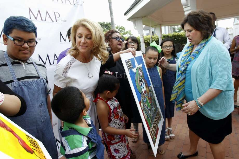 Sen. Wendy Davis, left, looks at one of the Loteria cards a student made for the fundraiser as Sen. Leticia Van de Putte signs one of the art pieces Thursday, July 24, 2014 during the Minority Advancement Project's annual shrimp boil at Heritage Park in Corpus Christi, Texas. The gubernatorial candidate also stopped by the Nueces County Democratic Party headquarters to greet phone bank volunteers during her visit. (AP Photo/Corpus Christi Caller-Times, Michael Zamora) Photo: Michael Zamora, Associated Press