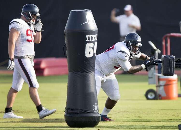 Day 4: July 29   Texans defensive end Jeoffrey Pagan, right, hits a
