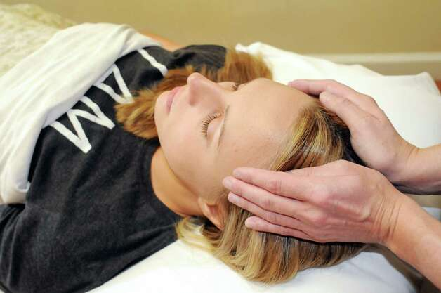 Dawn Kassirer of Ballston Spa receives an energy massage from Reiki practitioner Melissa Carter, owner of Wholistic Package, on Friday, July 25, 2014, at The Healing Spirit Center in Saratoga Springs, N.Y. (Cindy Schultz / Times Union) Photo: Cindy Schultz / 00027925A
