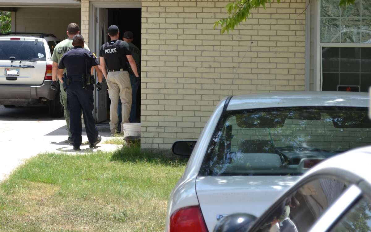 Officers prepare to make an arrest of a suspect in Seguin gang sweep.