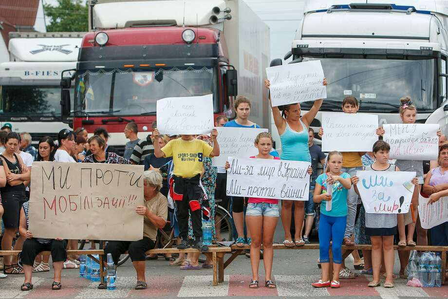Residents of Rakoshyno village hold peace signs while blocking a highway in western Transcarpathia province. Photo: Alexander Zobin, AFP/Getty Images