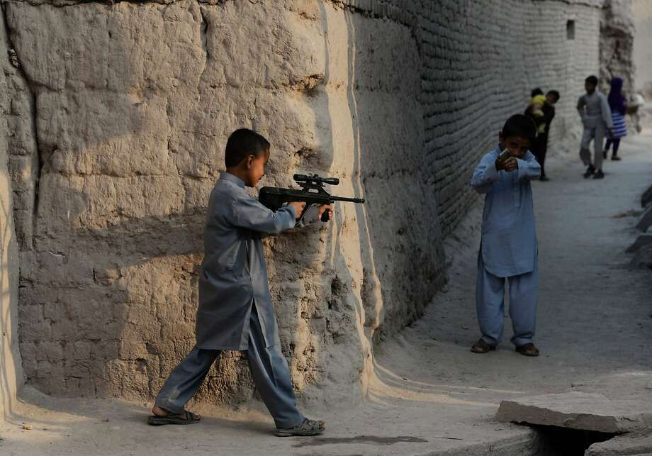 I shot you first!Afghan boys fire plastic guns at each other as they celebrate Eid al-Fitr and the end 