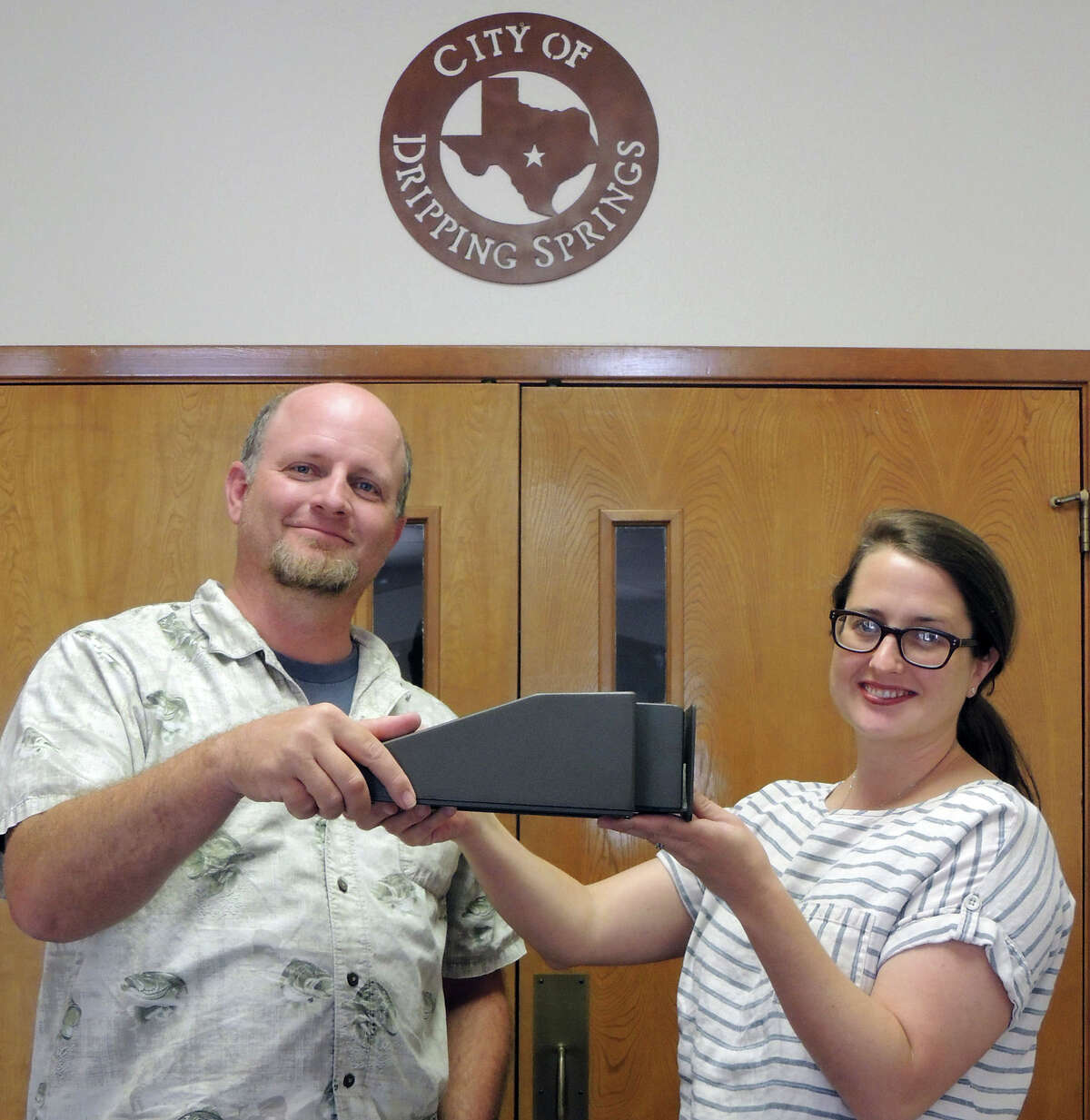 Dripping Springs City Planning Director Jon Thompson (left), and Deputy City Administrator Ginger Faught, show a sample of a dark-sky-friendly light fixture used in their city. Dripping Springs is the first city in Texas to be designated an International Dark Sky Community.Click through the slideshow to see all seven Dark Sky-Communities in the world.