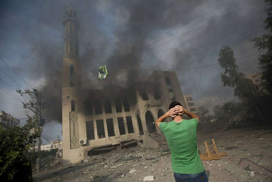 Bombed mosque: A Palestinian man holds his head in anguish as a mosque burns following an Israeli air strike in 