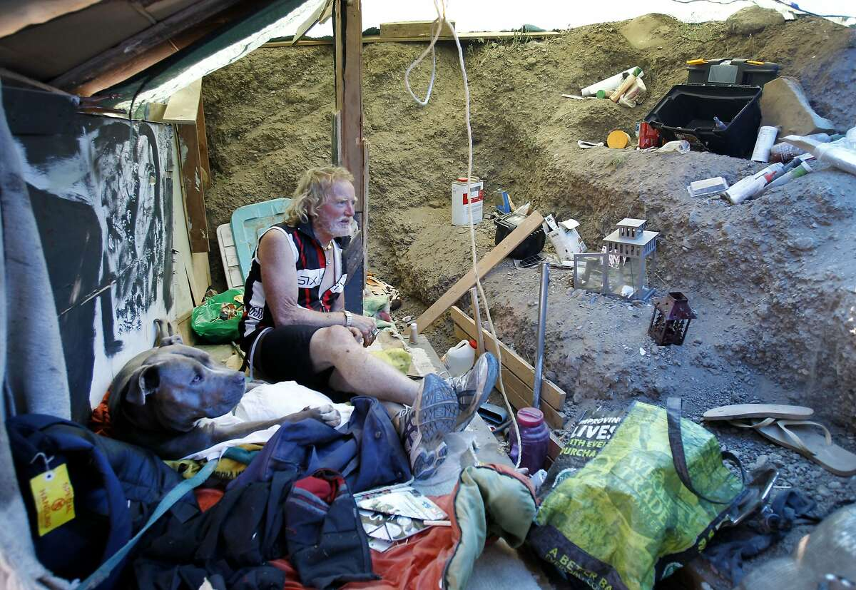 Danny, a homeless man and his dog, share a large space against a terraced hillside on the vacant lot in Berkeley, Calif. A homeless community that began in Albany, then moved to the Gilman Street freeway underpass in Berkeley, Calif. has scattered, although some are now in a vacant lot off Second Street.