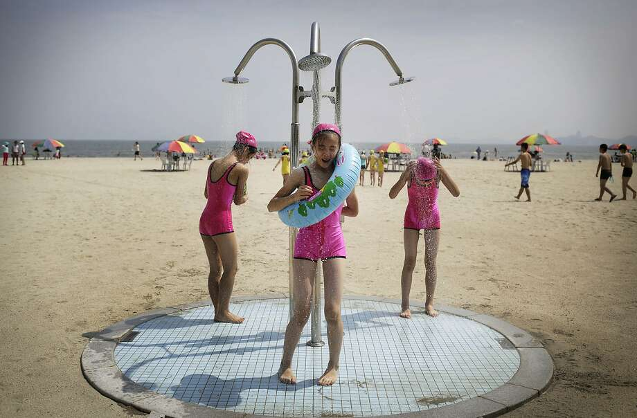 North Korean girls in similar bathing suits stand under a shower at the Songdowon International Children's Camp, Tuesday, July 29, 2014, in Wonsan, North Korea. The camp, which has been operating for nearly 30 years, was originally intended mainly to deepen relations with friendly countries in the Communist or non-aligned world. But officials say they are willing to accept youth from anywhere - even the United States.  (AP Photo/Wong Maye-E) Photo: Wong Maye-E, Associated Press