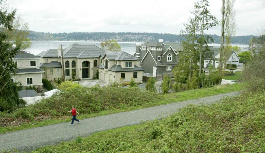 Carol Rogalski, who lives along the East Lake Sammamish Trail, walks along a section of the trail bordered by large homes on Sunday, April 9, 2006. Photo by Dan DeLong Photo: DAN DeLONG, P-I File Photo