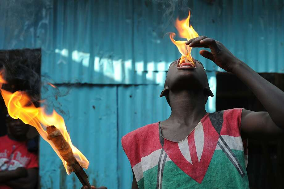 "A call for peace amid Kenya violence: A member of a youth corps campaigning for peace performs an fire-breathing act at the sprawling Kibera slum in Nairobi. Kenya takes pride in being a union of ""42 tribes,"", but a string of attacks in towns on its volatile coast has exposed bitter and explosive ethnic tensions linked to politics. Photo: Tony Karumba, AFP/Getty Images"