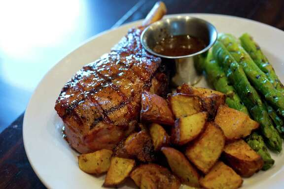 Grilled pork chops prepared by The Republic Grille at 4775 W Panther Creek Dr #490, The Woodlands, TX. (Billy Smith II / Houston Chronicle)