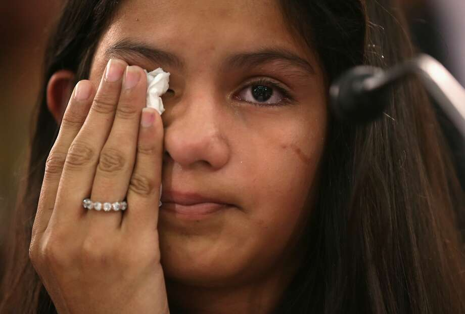 Mayeli Hernandez, 12, wipes away tears during a hearing before the Congressional Progressive Caucus on Capitol Hill as she tells her story of escaping her home country of Honduras last year. Photo: Alex Wong, Getty Images