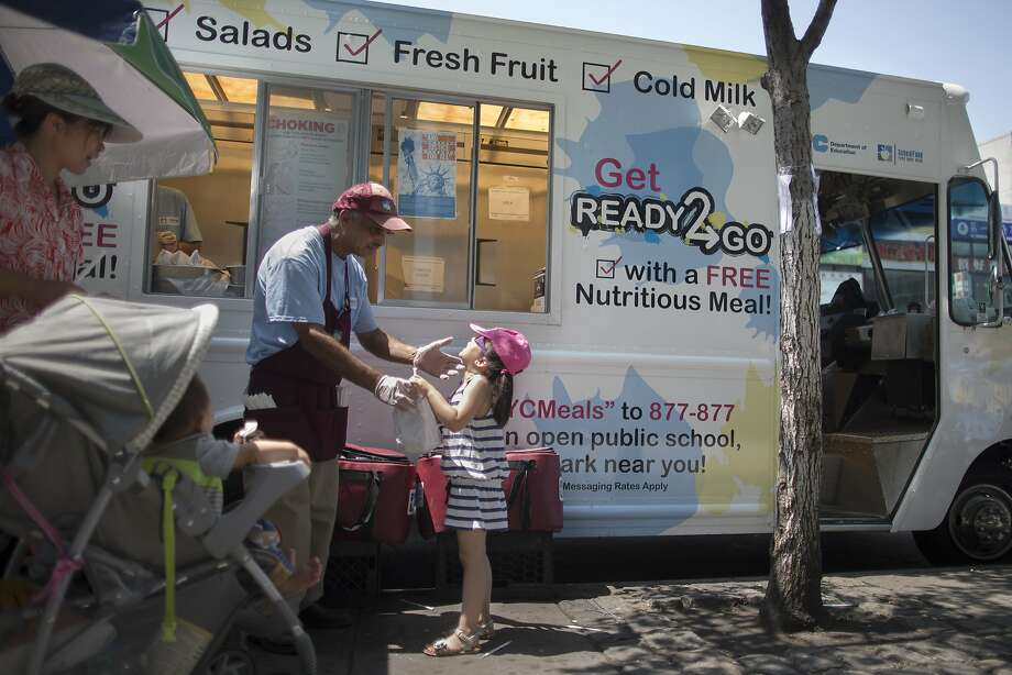 Children get free lunches at a food truck in the Flushing neighborhood of Queens through a summer meals program. Photo: John Minchillo, Associated Press