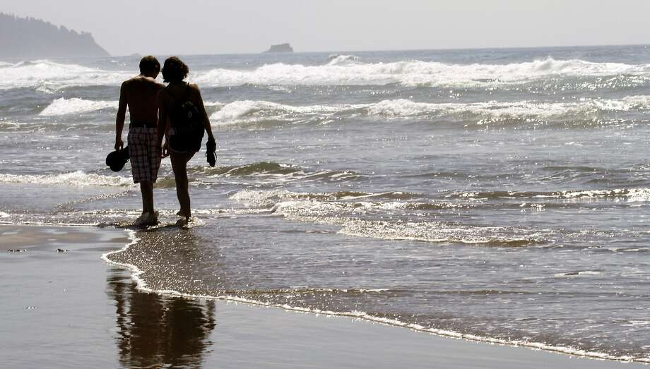 FILE - In this Aug. 26, 2010 file photo, a couple walks through the surf together in Cannon Beach, Ore. OKCupid on Monday, July 28, 2014 became the latest company to admit that it has manipulated customer data to see how users of its dating service would react to one another. (AP Photo/Don Ryan, File) Photo: Don Ryan, Associated Press