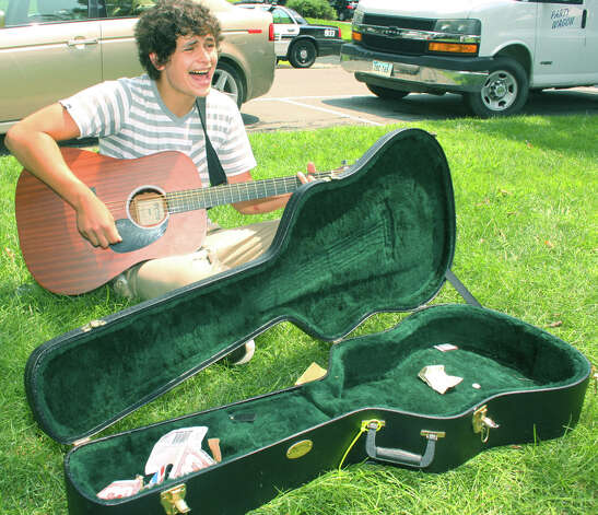 Austin Gold, 16, of New Milford tunes up by performing for passersby before hitting the stage at the Greater New Milford Chamber of Commerce's 47th annual Village Fair Days for July 25-26, 2014 on the Village Green. Photo: Walter Kidd / The News-Times Freelance