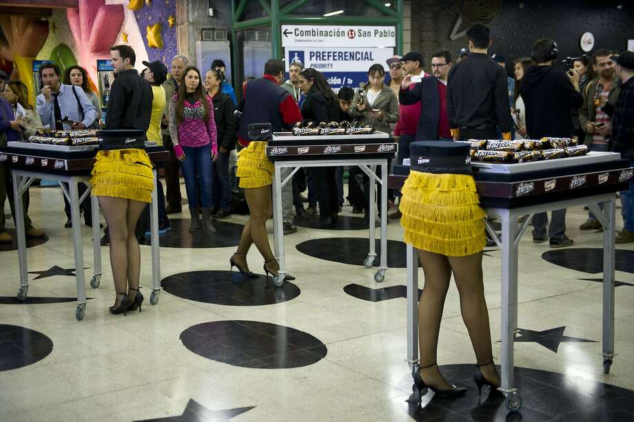 Topless magic show: During a promotion for a magician in Santiago, models apparently missing the upper halves of their bodies serve cookies to passing commuters in the subway. Photo: Martin Bernetti, AFP/Getty Images