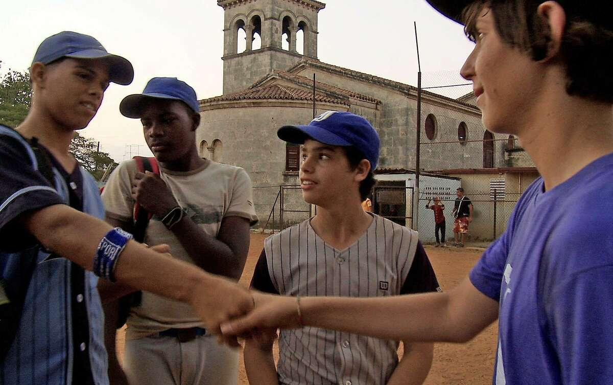 Mica (right) chats with ballplayers his age in Havana after delivering gear. Mica chats with ballplayers his age in Havana after delivering gear.