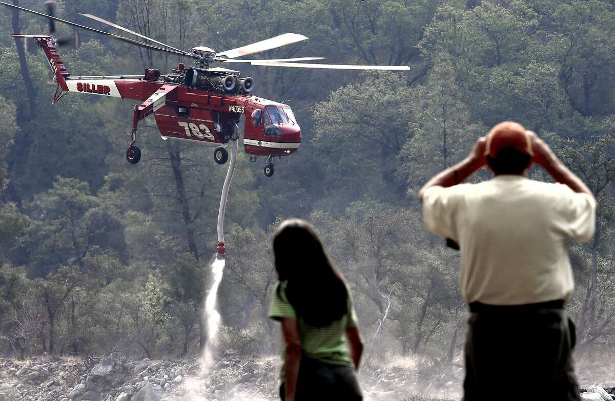 Patsy and John West visiting from Maryland watch as a helicopter takes on water from the Merced River, as firefighters continue to battle the El Portal fire just west of Yosemite National Park on Tuesday July 29, 2014, in El Portal, Calif.
