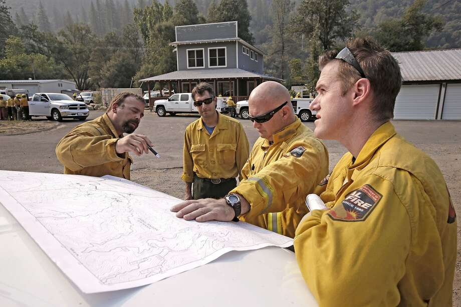 (l to r) Mike DeMillo, US forest service, Tomas Gonzales, US forest service, Noah Byrne, Cal fire and Thomas Shoots, Cal fire map out their plans for the day, as firefighters continue to battle the El Portal fire just west of Yosemite National Park on Tuesday July 29, 2014,  in El Portal, Calif. Photo: Michael Macor, The Chronicle