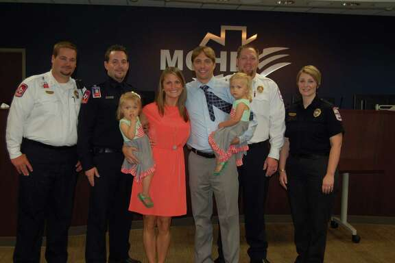 Bobby and Leighann Bailie and their twin daughters, Eloise and Marguerite, attend a reunion with members of a Montgomery County emergency response team who were involved in the rescue of Eloise last summer after she fell into a pool and nearly drowned. In addition to the twins, the photo shows, from left to right, Matthew Walkup, Kevin Crocker, Leighann Bailie, Bobby Bailie, Kevin Nutt and Kim Brown.  (Photos by Montgomery County Hospital District & Public Health District)