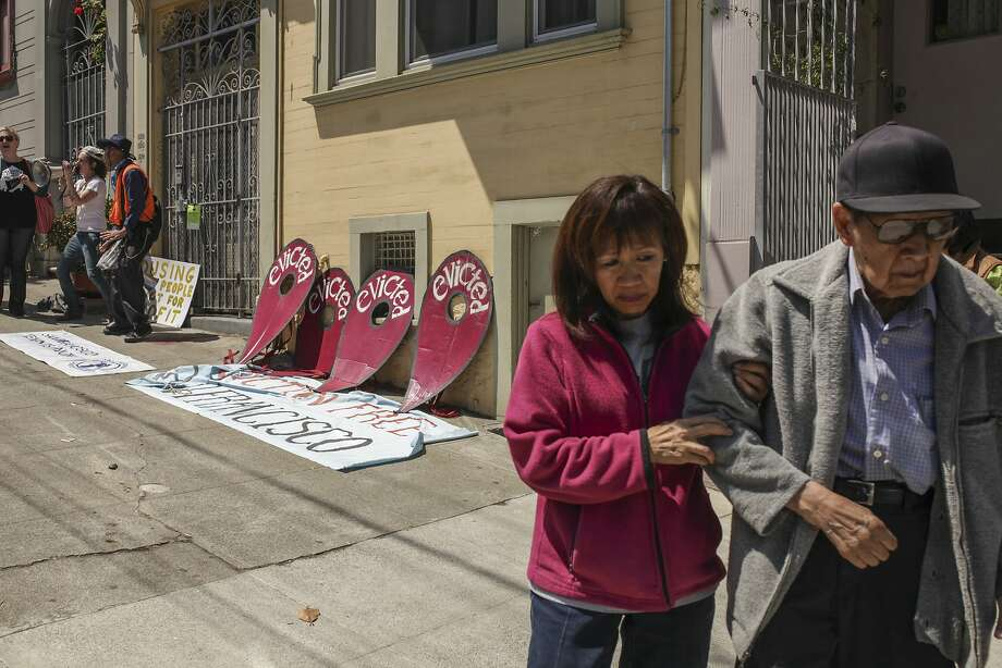 Pedestrians walk past a protest campaign in association with the San Francisco Tenants Union against the Ellis Act evictions of tenants in a building and subsequent vacation rental of the units. Photo: Sam Wolson, Special To The Chronicle