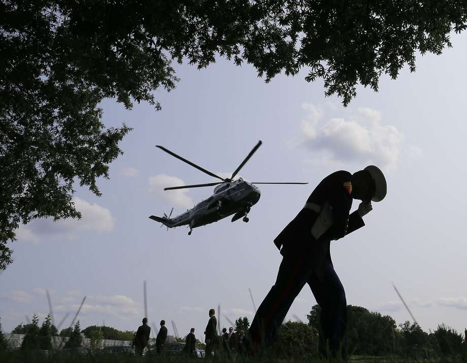 A Marine honor guard braces himself from the rotor wash of Marine One helicopter as President Barack Obama lands at Walter Reed National Military Medical Center to visit with wounded military personnel in Bethesda, Md., Tuesday, July 29, 2014. (AP Photo/Charles Dharapak) Photo: Charles Dharapak, Associated Press