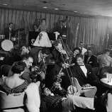 """The swing legend Louis Prima moved to Las Vegas in 1954 after he was offered to perform with his wife Keely Smith as a resident act at The Sahara Hotel and Casino.In the time that Prima and Smith were a hot Vegas act, they released some of their most famous pieces including """"Just A Gigolo,"""" """"I Ain't Got Nobody,"""" and """"Old Black Magic.""""With all the success, Prima and Smith moved to a higher paying gig at the Desert Inn. Eventually the performances took too much of a toll on Prima and Smith's marriage, which resulted in Smith filing for divorce after their contract at the Desert Inn wrapped up in 1961.Pictured: Jazz trumpeter Louis Prima blowing horn while lying on floor w. wife, singer Keely Smith, standing on bandstand in background."""
