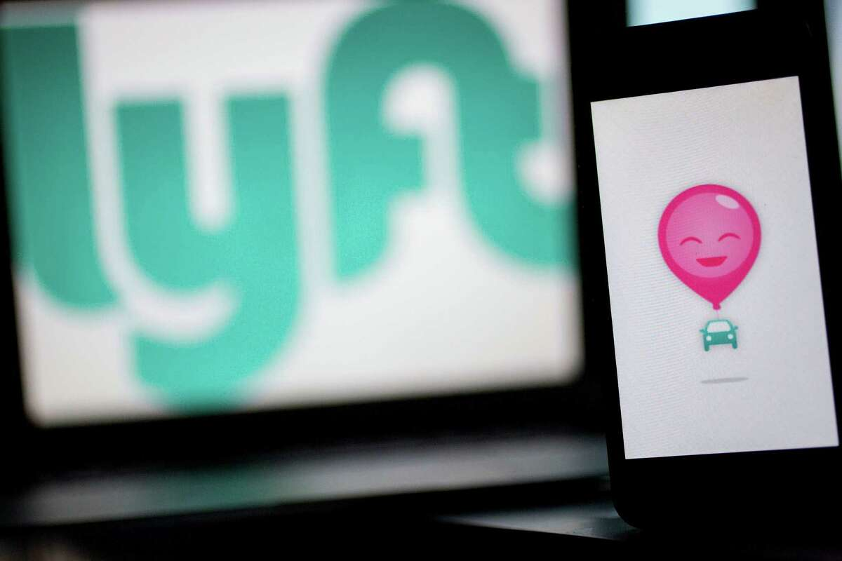 The Lyft Inc. logo and application (app) is displayed on an Apple Inc. iPhone 5s and MacBook Air for an arranged photograph in Washington, D.C., U.S., on Wednesday, July 9, 2014. Lyft Inc. is taking its ride-sharing service into New York this week and is abandoning its trademark pink mustaches in the process, taking on rival Uber Technologies Inc. in one of the biggest U.S. markets. Photographer: Andrew Harrer/Bloomberg