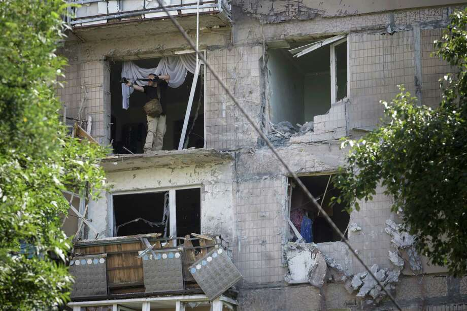 A photographer leans from a damaged residential apartment house Tuesday after shelling in Donetsk, eastern Ukraine. Local residents said the shelling came from the direction of the Ukrainian army's positions. Photo: Dmitry Lovetsky, STF / AP