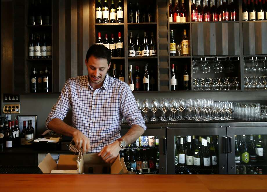 Ryan Cole stocks the bar with wine at his Russian Hill restaurant, Stones Throw. Cole is offended by the disruptive new practice of charging to snag coveted restaurant reservations. Photo: Brant Ward, San Francisco Chronicle