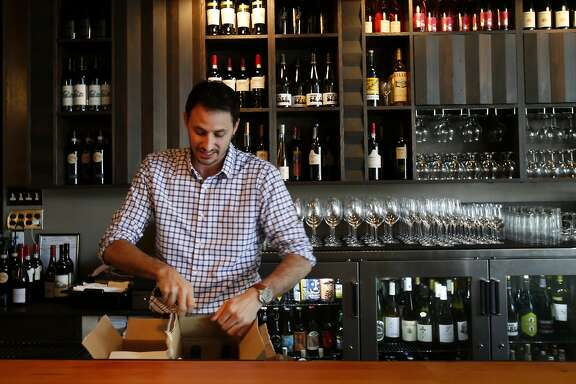 Ryan Cole stocks his bar with wine before guests will arrive Tuesday July 29, 2014 in San Francisco, Calif. Restaurant owner Ryan Cole is concerned about the growing number of reservation apps that charge customers and are circling the city's hottest restaurants such as his on Russian Hill called Stones Throw.