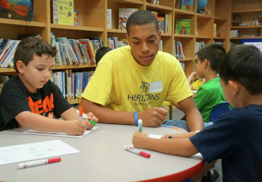 Brunswick School rising senior Clayton Adams works with rising second-graders J.P. Robledo, left, and Ziren Nael on a math problem during a class on Tuesday, July 29 at Brunswick's Horizons summer program. Photo: Paul Schott / Greenwich Time