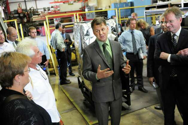 Lou Okonski, CEO of Evoworld Inc. and Troy Boilerworks, center, leads a tour following a news conference on Tuesday, July 29, 2014, at Evoworld Inc. in Troy, N.Y. NYSERDA and the DEC announced a roll-out of a comprehensive set of programs under Gov. Andrew Cuomo's Renewable Heat NY initiative. (Cindy Schultz / Times Union) Photo: Cindy Schultz / 00027962A