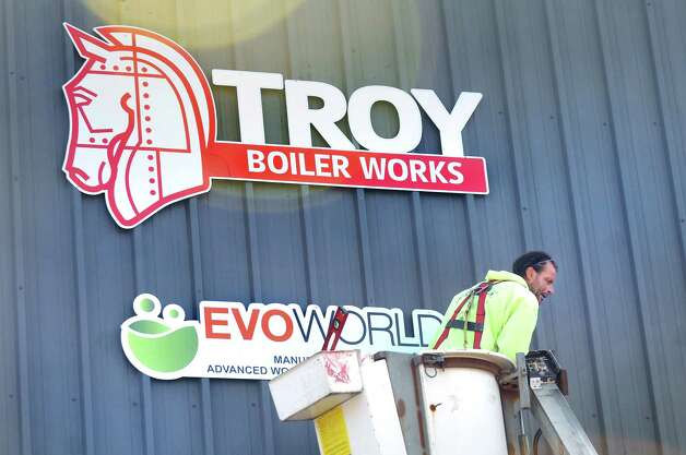 Bob Carpenter of Sign Studio finishes installing a sign on Tuesday, July 29, 2014, at Evoworld Inc. in Troy, N.Y. NYSERDA and the DEC announced a roll-out of a comprehensive set of programs under Gov. Andrew Cuomo's Renewable Heat NY initiative. (Cindy Schultz / Times Union) Photo: Cindy Schultz / 00027962A