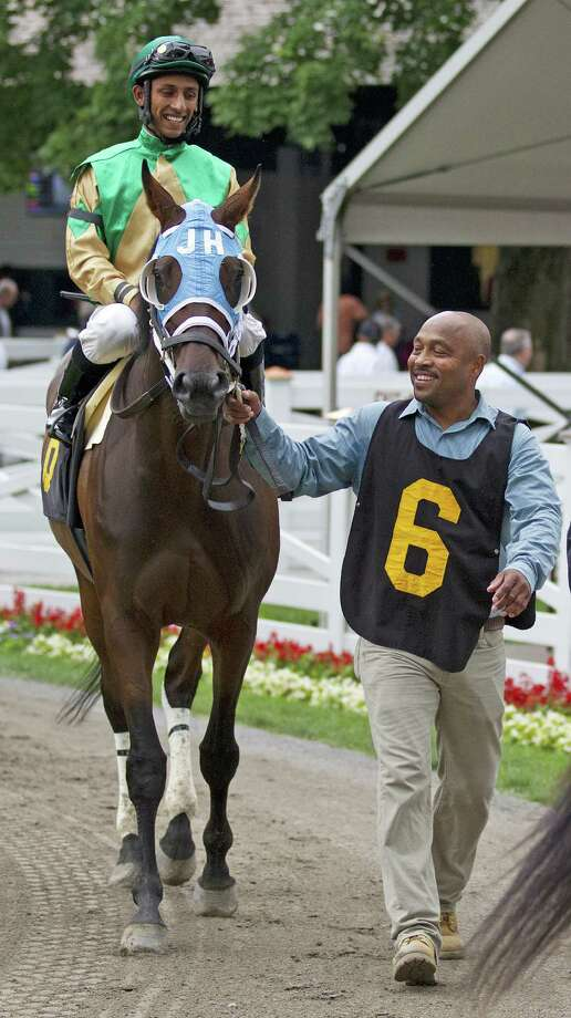 Omar Aquino leads Here He Fitz with jockey Rajiv Maragh to the track. (Tom Keyser) / © 2014 Tom Keyser All rights reserved