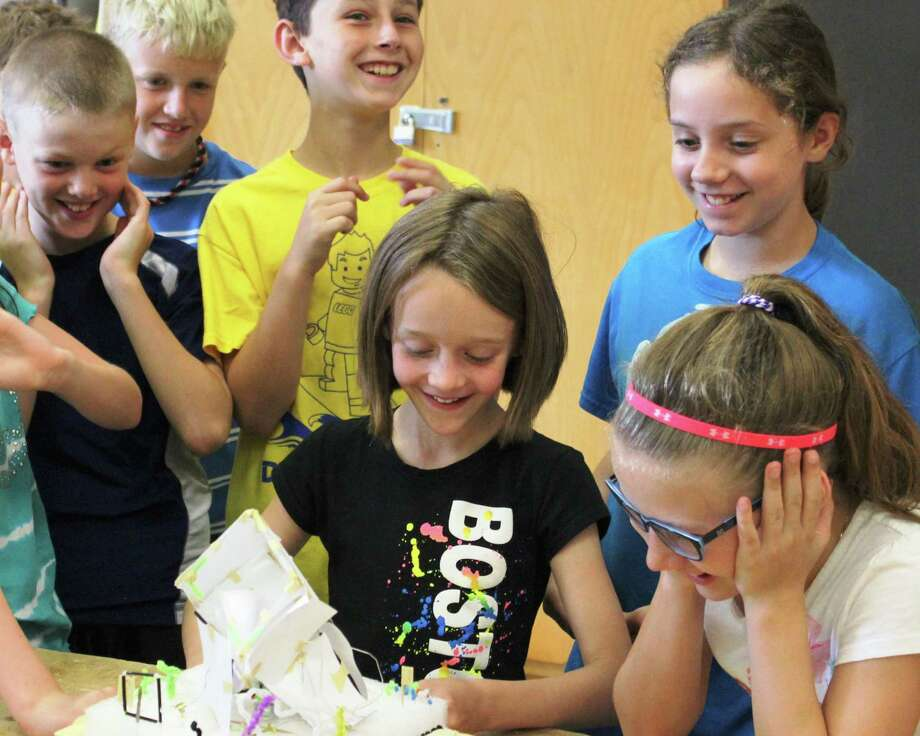 """Natalie Arndt, center, and other Ballston Spa students react to the collapse of a structure while being tested on a """"Shake Table"""" during their summer enrichment course. The district was able to offer the experience at a nominal cost to families as a result of a grant from Time Warner Cable. (Stuart Williams)"""