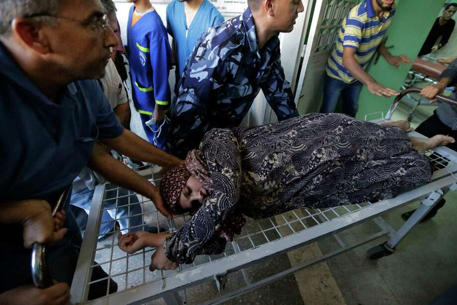 A Palestinian woman wounded in an Israeli strike on a Gaza Strip refugee camp is wheeled into an emergency room on Tuesday. Photo: Lefteris Pitarakis, STF / AP