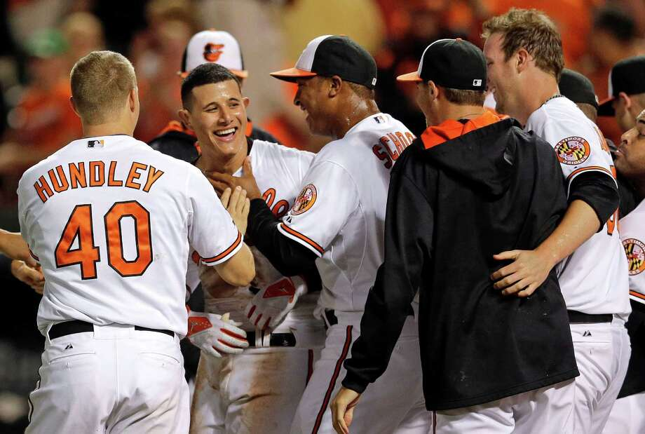 Baltimore Orioles' Manny Machado, second from left, celebrates with teammates after hitting a game-winning solo home run in the 12th inning of a baseball game against the Los Angeles Angels, Tuesday, July 29, 2014, in Baltimore. Baltimore won 7-6. (AP Photo/Patrick Semansky) ORG XMIT: MDPS110 Photo: Patrick Semansky / AP