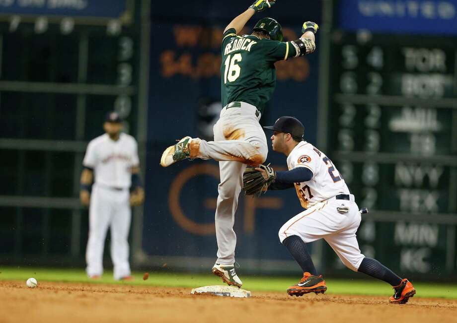 A's right fielder Josh Reddick does a dance atop second base as Jose Altuve chases an errant throw during a ninth inning in which the Astros gave up six runs on six hits, walked two batters and threw a wild pitch. Photo: Karen Warren, Staff / © 2014 Houston Chronicle