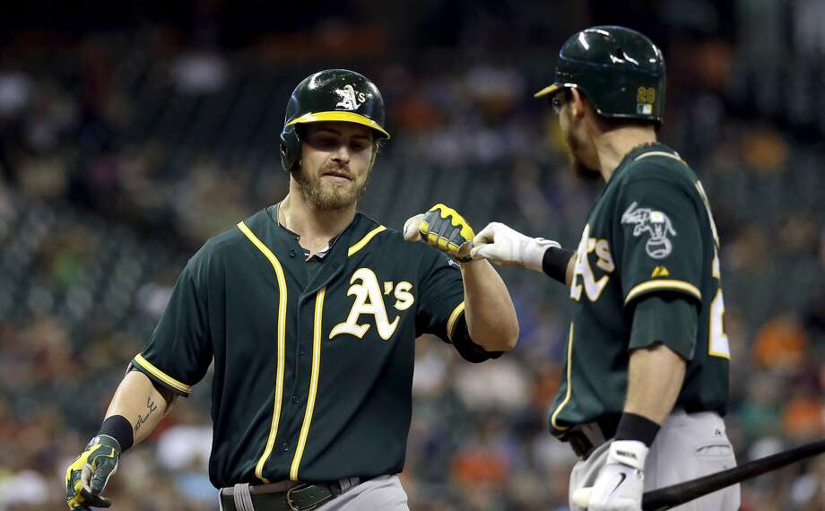 Josh Reddick (left), playing center for the first time since 2012, is congratulated by Eric Sogard after his fifth-inning homer. Photo: David J. Phillip, Associated Press