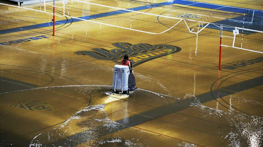 A worker begins the task of cleaning up at least an inch of water covering the playing floor at Pauley Pavilion, home of UCLA basketball, after a broken 30-inch water main under nearby Sunset Boulevard caused flooding that inundated several areas of the UCLA campus in the Westwood section of Los Angeles on Tuesday, July 29, 2014. (AP Photo/Mike Meadows) Photo: Mike Meadows, Associated Press