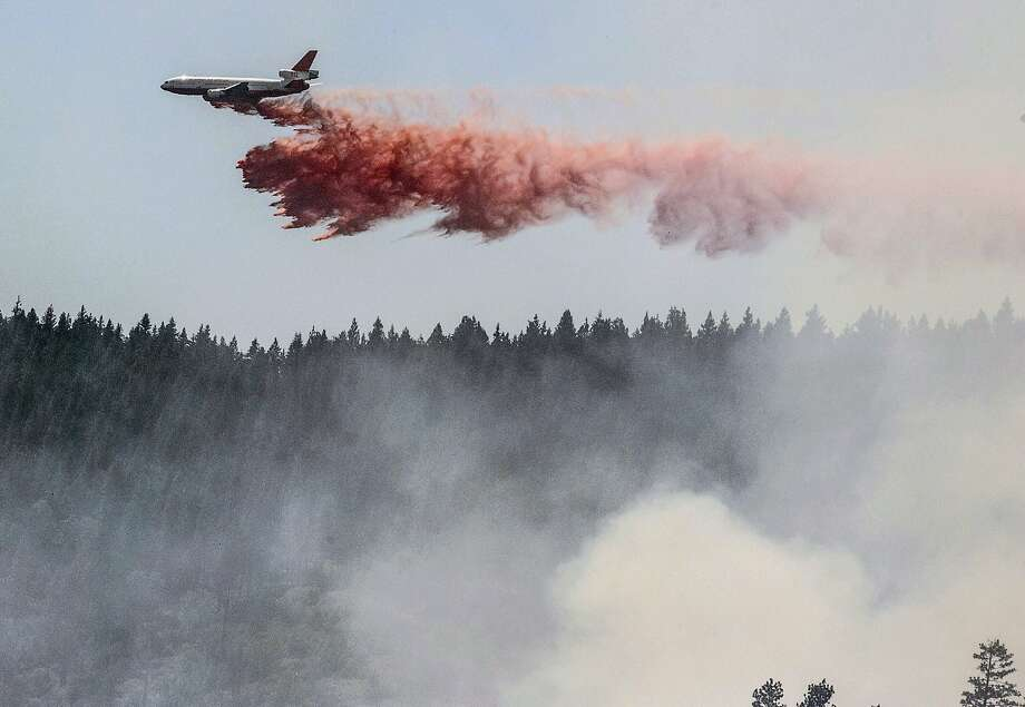 A plane drops fire retardant as firefighters battle a blaze in El Portal, Calif., near Yosemite National Park on Tuesday, July 29, 2014. Firefighters in the state are also battling another wildfire in the Sierra Nevada foothills east of Sacramento. (AP Photo/Al Golub) Photo: Al Golub, Associated Press