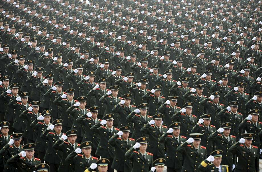 Chinese paramilitary policemen take a pledge to ensure the security during the upcoming Youth Olympic Games in Nanjing, in east China's Jiangsu province Tuesday, July 29, 2014. The Games will be held in Nanjing from Aug. 16 to 28. (AP Photo) CHINA OUT Photo: Associated Press