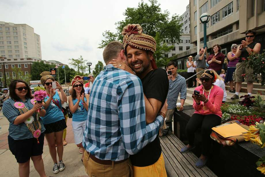 FILE - Todd Kinsman, 28, left, and Ravi Manghnani, 37, hug after getting married in Madison, Wis., a day after the ban on same-sex marriage was struck down. The Wisconsin Supreme Court announced Tuesday, July 29, 2014 that it will release a highly anticipated decision Thursday dealing with the state's domestic partnership registry. (AP Photo/Wisconsin State Journal, Amber Arnold, File) Photo: Amber Arnold, Associated Press