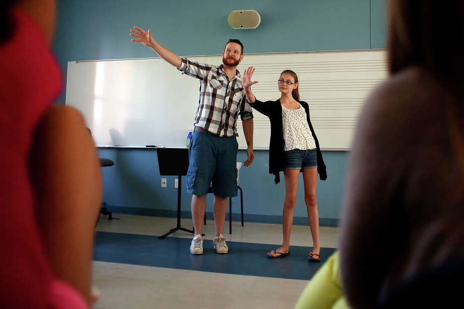 Instructor Matthew Olmstead, left, instructs Catie Van Luven on how to present herself when performing a song during the Summer Academy for Youth pop singer bootcamp Monday, July 28, 2014, at the College of St. Rose in Albany, N.Y.  The camp is for children grades 6-10 and covers sports, theater, writing, arts and sciences. (Tom Brenner/ Special to the Times Union) Photo: Tom Brenner / ©Tom Brenner/ Albany Times Union