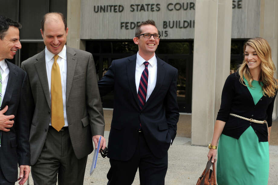 Johnathan Nathans, center, a former Bridgeport Bluefish player, leaves Federal Court in Bridgeport, Conn. after receiving a favorable verdict in his lawsuit against Jose Offerman, a former Long Island Ducks player who charged the pitcher's mound swinging a bat during a 2007 game. Nathans, a catcher for the Bluefish, said that he was injured in the incident, and was awarded $940,000. He is seen here with his wife, Kate Lawrence, and attorneys Josh Koskoff, far left, and Craig Smith. Photo: Ned Gerard / Connecticut Post