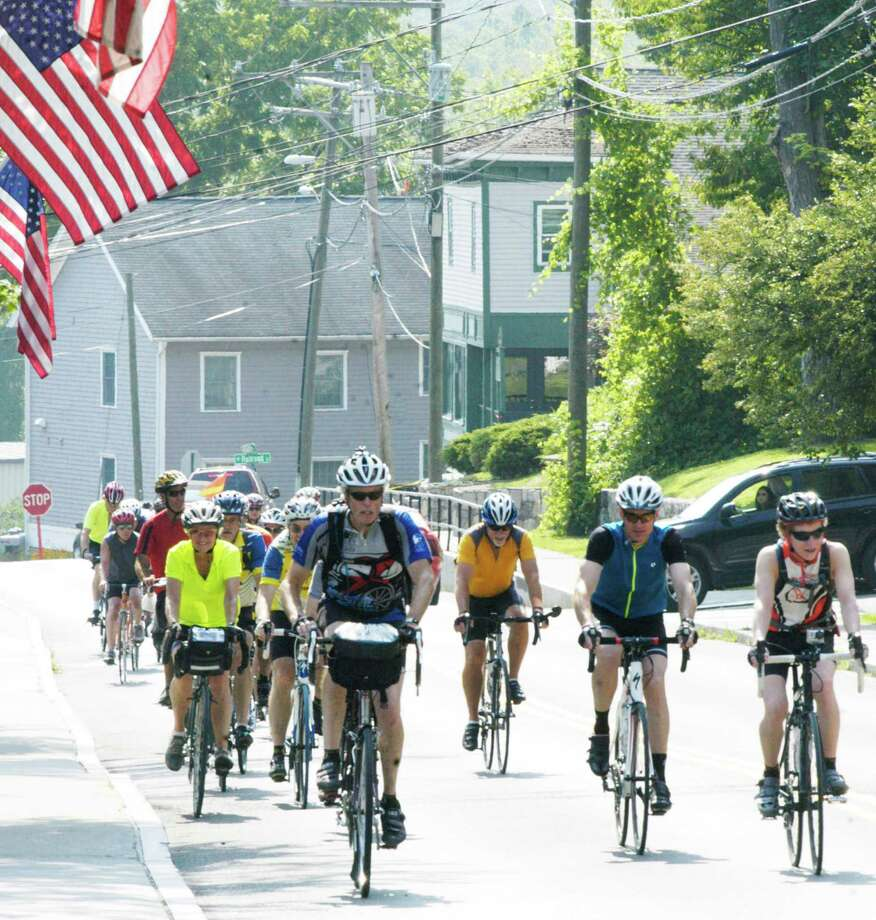 Tom O'Brien, left foreground, and his son, Jake, 16, right, lead the way Friday along Bennitt Street as cyclists complete their 289-mile Greenway ride from near Burlington, Vermont to New Milford. July 25, 2014 Photo: Norm Cummings / The News-Times