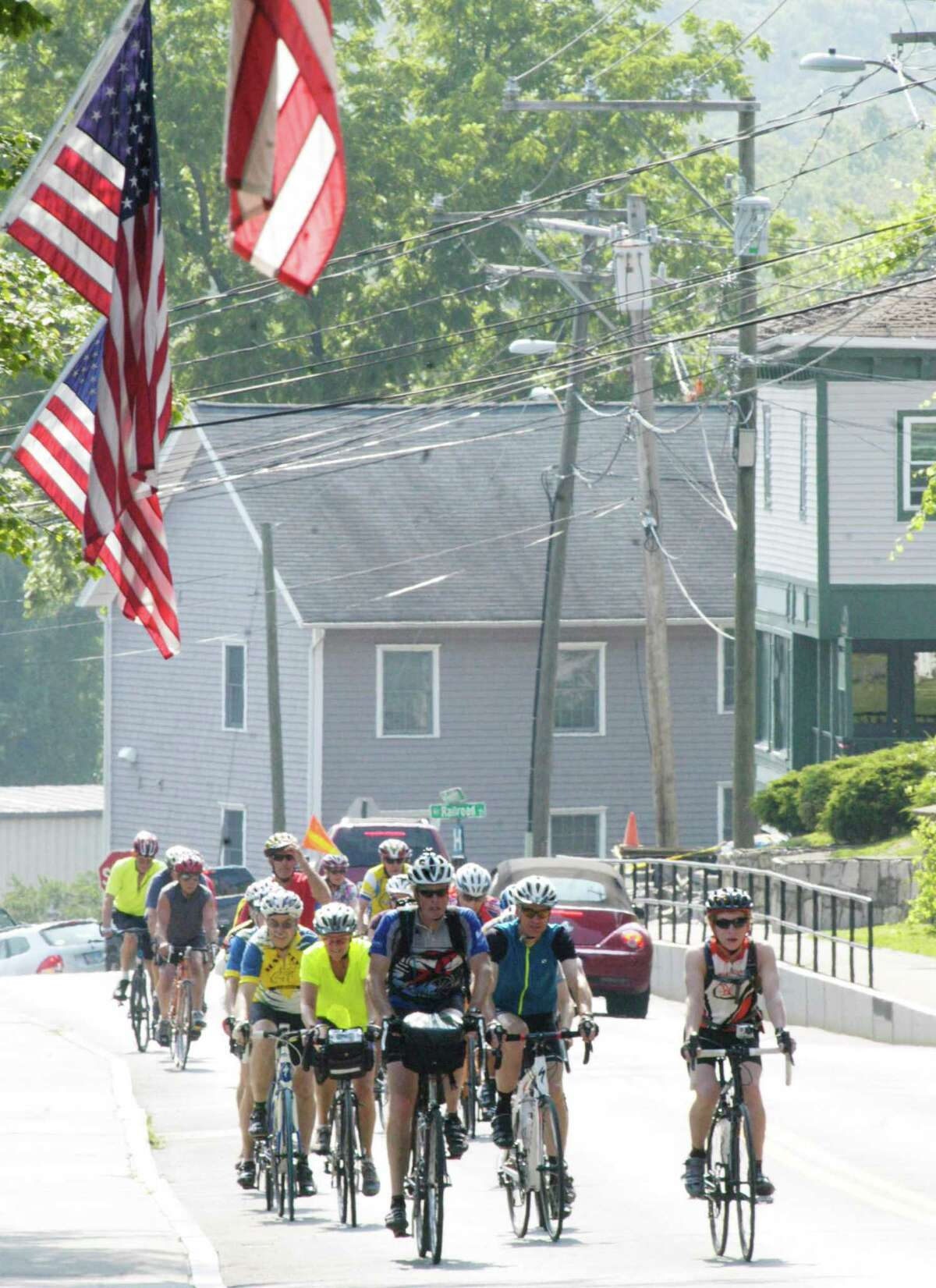 Tom O'Brien, left foreground, and his son, Jake, 16, right, lead the way Friday along Bennitt Street as cyclists complete their 289-mile Greenway ride from near Burlington, Vermont to New Milford. July 25, 2014